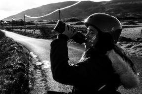 Black and white photo of a cyclist who drinks water