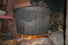 a cauldron stands on a wood stove