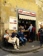 talking men sitting on street at wall of Restaurant, italy, florence