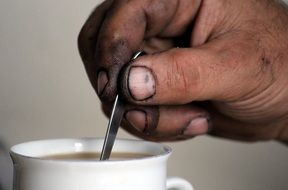 a man mixes coffee with a spoon
