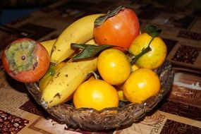 tangerines, bananas and persimmons in a transparent bowl