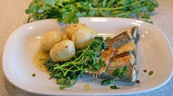 fish with potatoes and spinach on a plate