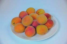 ripe apricots on a white plate