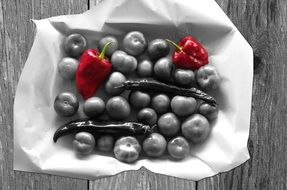 black and white photo of tomato, chili pepper and red pepper in a basket