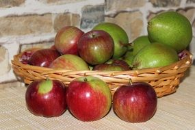 green pears and red-green apples in a wicker basket