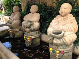 Buddha statues in a pond at the entrance to a restaurant in the Philippines