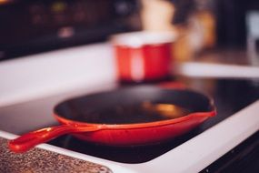 red frying pan heated on the stove in the kitchen