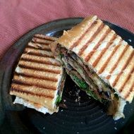 grilled sandwich on a black plate