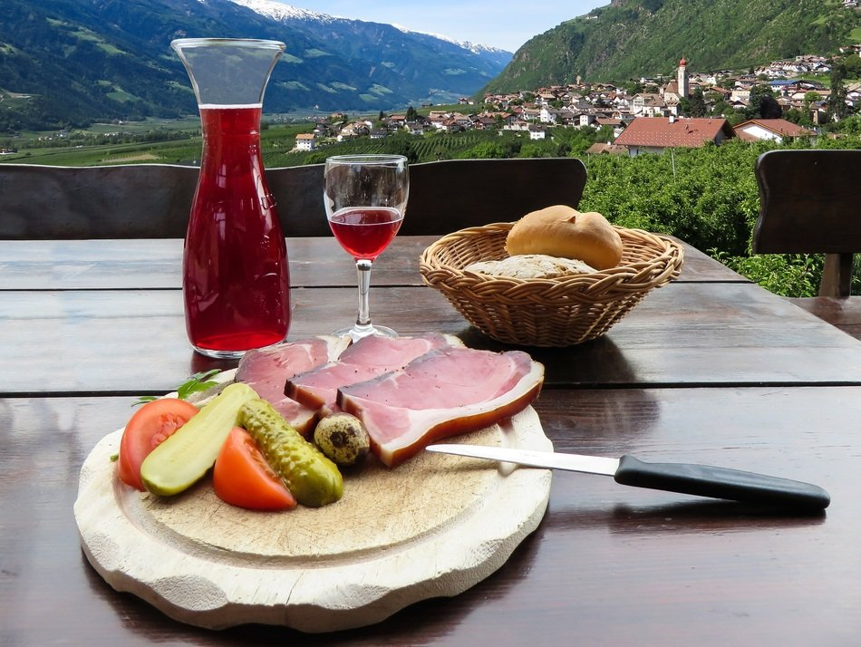 cold appetizers, bread basket and carafe with red wine against the background of South Tyrol