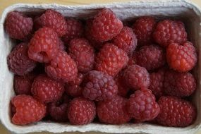 ripe raspberries in a cardboard box