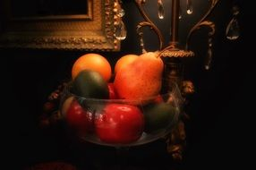 fruits in a bowl on a table in the dark