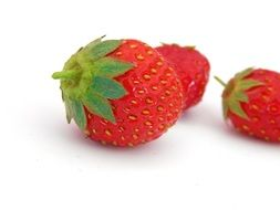 red strawberries with green ponytails on a white surface