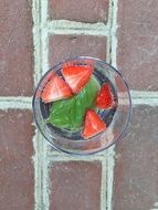 Sliced strawberries with basil in a glass