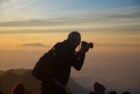a photographer is taking pictures of mountain sunset