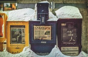 multi-colored newsstands under the snow
