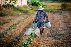 man with watering can on a farm field