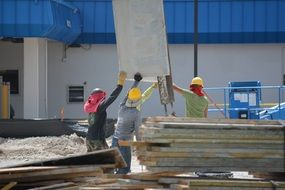 workers at a construction site near planks