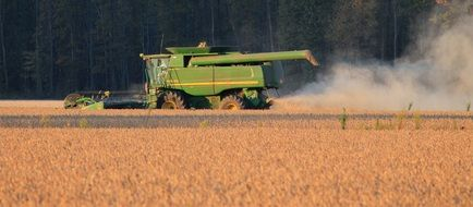 green harvester on the field is harvesting