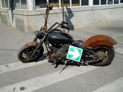 vintage motorcycle with direction sign on street