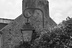 black and white photo of a lamp on a stone wall