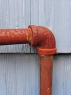 elbow of a metal pipe near the wall