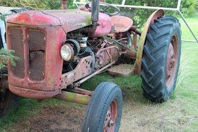 old tractor stands on green grass