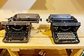 two typewriters on a wooden table