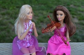 Barbie doll plays the violin near her friend