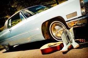 silver cowboy boots, guitar and vintage car