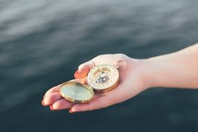 compass in hand above water