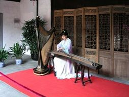 Asian girl is playing a musical instrument in China