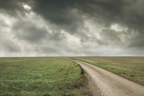 road along the fields on the background of a stormy sky