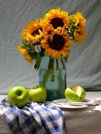 still life a bouquet of sunflowers and green apples