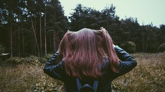 a brown-haired girl stands with her back against a dense forest