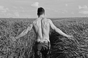 black and white photo of a naked man on a wheat field