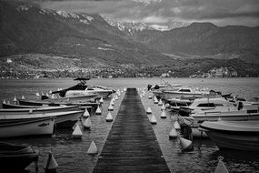 black and white photo of boats at a wooden pier on a background of mountains