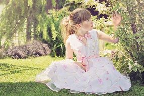 little girl in a light beautiful dress in a sunny garden