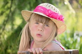 Girl in a straw hat with a pink bow