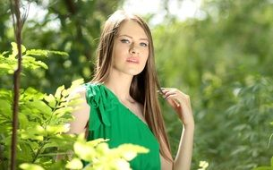girl with long hair and in a green dress in a sunny forest