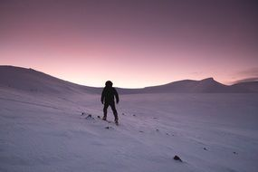 hiker in the snowy mountains at dusk