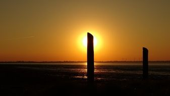 pillars on the shore of the North Sea against the backdrop of a golden sunset