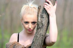 photo of a blonde at a tree trunk