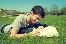 a man writes a letter while lying on green grass