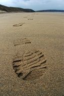footprint of shoes on wet sand at the beach
