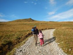 parent and child walk along a mountain path