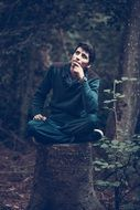 pensive young man sitting on a stump in the forest