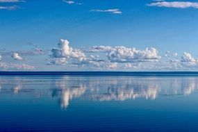 white clouds reflected in the blue water of the ocean