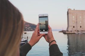 girl photographs a port in Dubrovnik, Croatia
