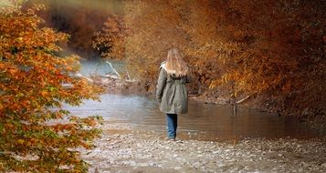 girl stands by the river near autumn trees