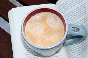 cup of coffee on the open book